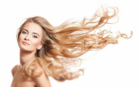 Die langen blonden Haare einer Frau wehen im Luftzug, sodass die Haarverlängerung gut zur Geltung kommt.