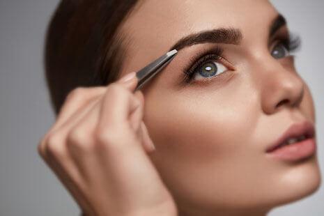 Eine dunkelhaarige Frau in Nahaufnahme zupft die Augenbraue des rechten Auges mit einer Pinzette.