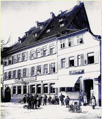"""Das alte Haus """"Zum Raben"""", rechts die Bäckerei Roth, abgebrochen 1908 - vor dem Hotel auch der oben erwähnte Handwagen"""