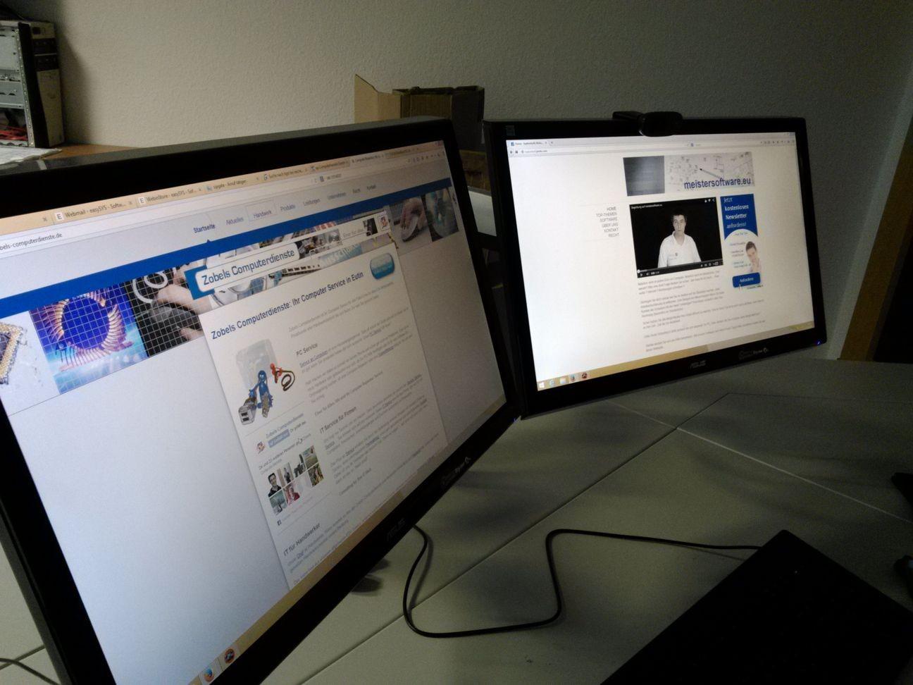große Monitore auf denen Zobels Computerdienste zu sehen ist