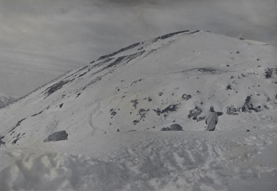 Ein Gebirgsschütze vor verschneiten Cukla. Die Spuren im Schnee zwischen der alten Österreich-Ungarischen Linie und der eroberten italienischen Line auf der Cukla datieren das Bild auf die Zeit nach der Einnahme des Gipfels. Sammlung Isonofront.de