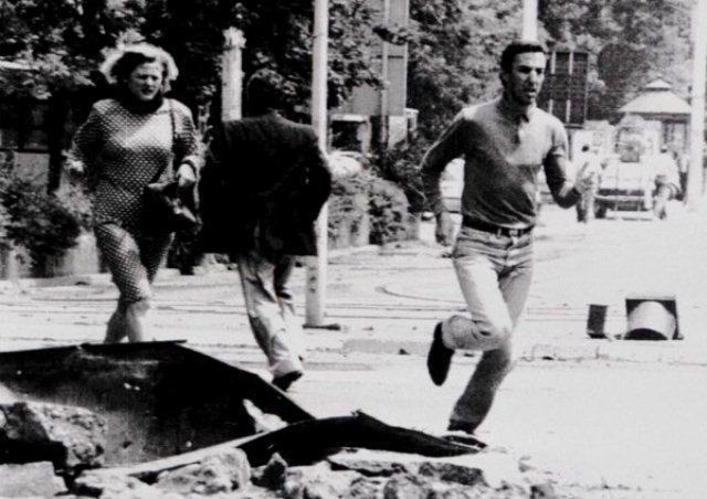 """Beboere i Sarajevo (13. juli 1992) løber gennem et område, der er markeret med skiltet: """"Pas på: Snigskytter!"""" Mange civile blev hver dag dræbt eller såret af snigskytter."""