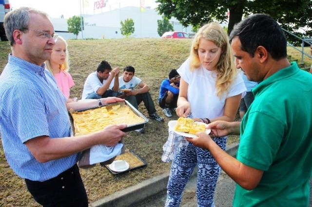 Roija (56) og Larissa (16) Weidhas fra  Dresden fordeler hjemmebagt æblekage til flygtninge i Heidenau.