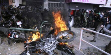 Demonstranter har trængt politistyrker op mod en mur og sat ild til deres motorcykler