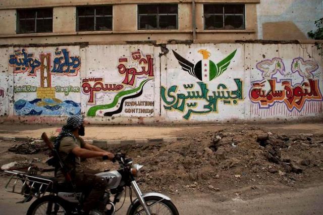 """På muren i baggrunden to graffitis: """"Revolutionen er fredelig"""" (t.h.) og """" Den Frie Syriske Hær"""" (andet billede t.h.)"""