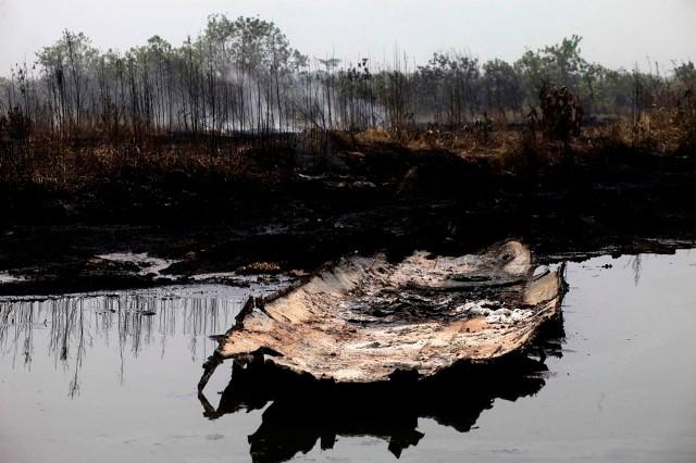 Et brændt kanoskrog hviler i en forurenet bæk efter en olie rørledning eksploderede ved landsbyen Arepo lige udenfor Lagos, d. 13. januar, 2013.