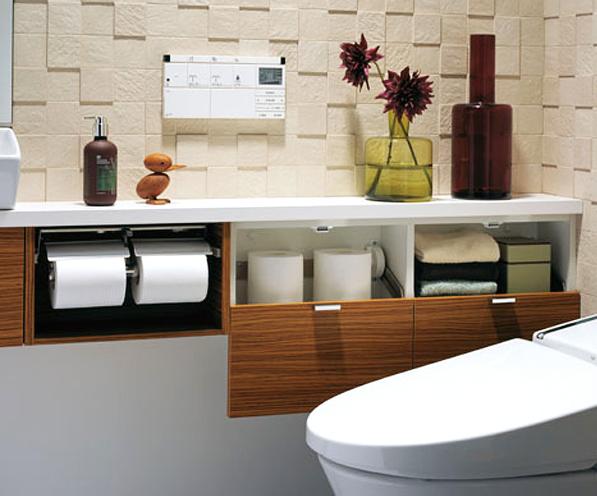 トイレの限られた空間での収納 / カウンターのデット空間に収納と紙巻器がセットされ、すっきりとしたデザイン。壁には凹凸のあるエコカラットを使用したぬくもりある北欧調の空間。