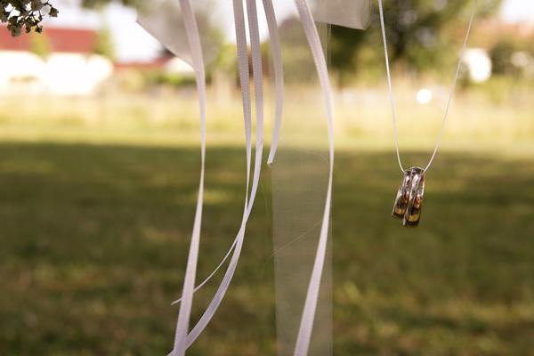 Die Eheringe hängen am Band des Brautstraußes