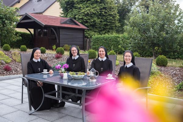 Schwesternkonvent um einen Tisch versammelt