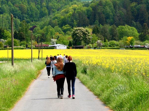 Jugendliche laufen entlang der Straße in Begleitung