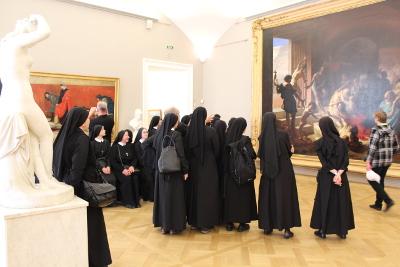 Eucharistinerinnen betrachten in der Gemeinschaft ein großes Gemälde