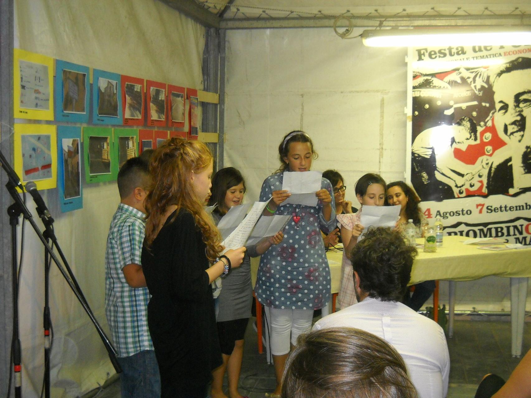 La recitazione collettiva delle poesie da parte dei piccoli attori.