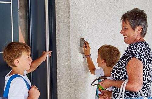 Familie öffnet Haustür mit ekey Fingerscanner
