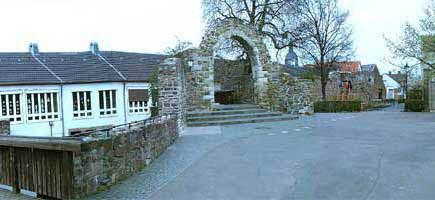 Durch diesen Torbogen kommen wir auf den Schulhof. Unter der Brücke ist der untere Schulhof, der von den 3. und 4.  Schuljahren genutzt werden darf.