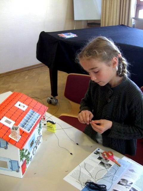 Eine Grundschülerin schließt den Schalter an den Stromkreislauf an.