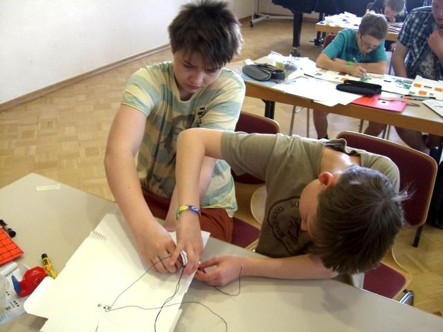 """Gemeinsam meistern die Schüler die schwierige Aufgabe, die Kabel der Lampen """"unter Putz"""" zu verlegen."""