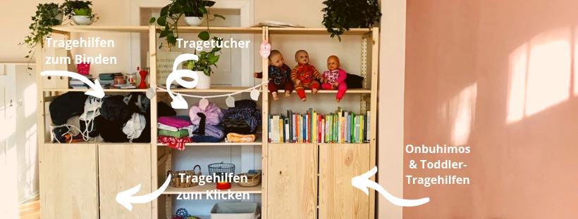 Das Bild zeigt ein Regal mit Tragetüchern, Tragehilfen und Tragepuppen zum Ausleihen (Tücherei) in Berlin