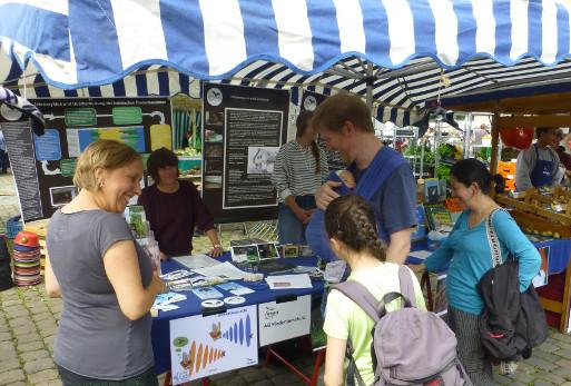 Frauke Meier, Theresa Kurth und Besucher am NABU-Stand auf dem Wochenmarkt