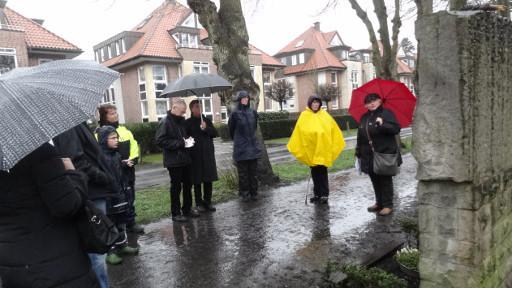 Marianne Feldmann (roter Schirm) von der Initiative Prozessionsweg erläutert die Kreuzwegsteine am Prozessionsweg Foto: Thomas Hövelmann