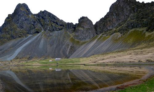 Ein kleines Gehöft im Spiegelbild eines Sees am nahen Atlantik.