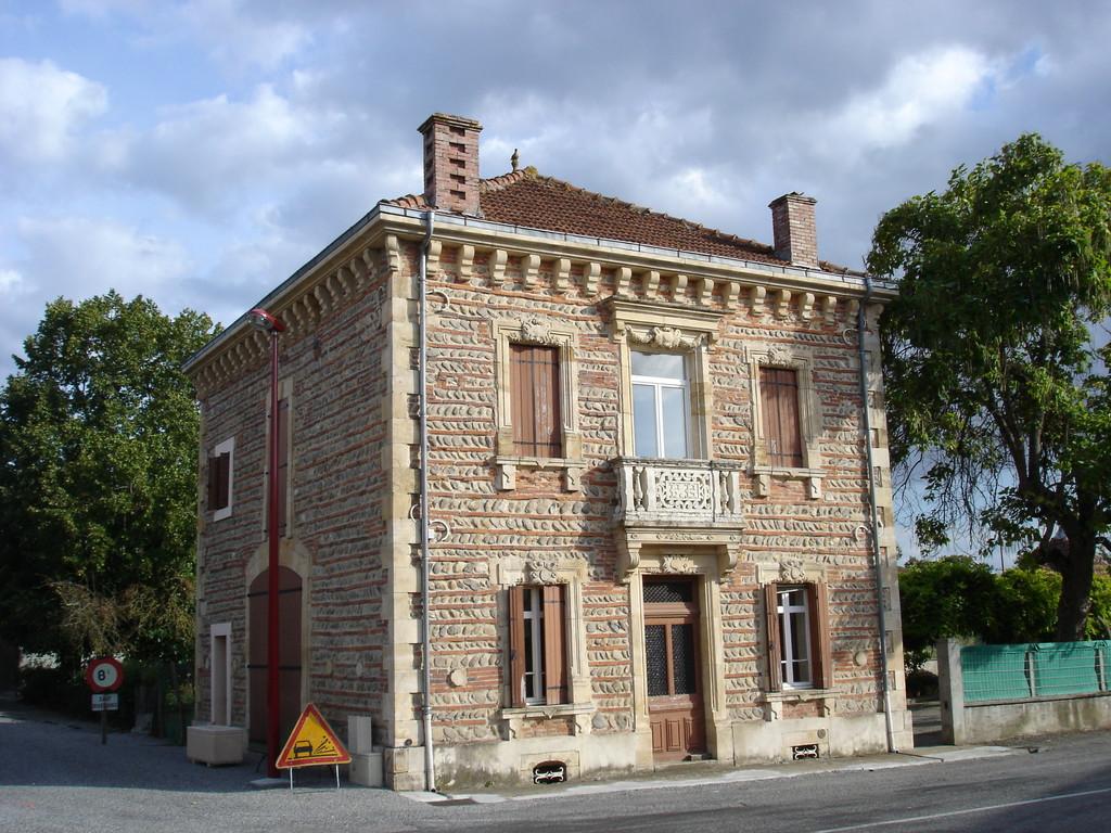 Maison de galets et briques ou à colombages dans centre village