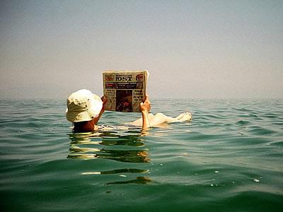 Touriste faisant semblant de lire l'arabe sur un journal local !