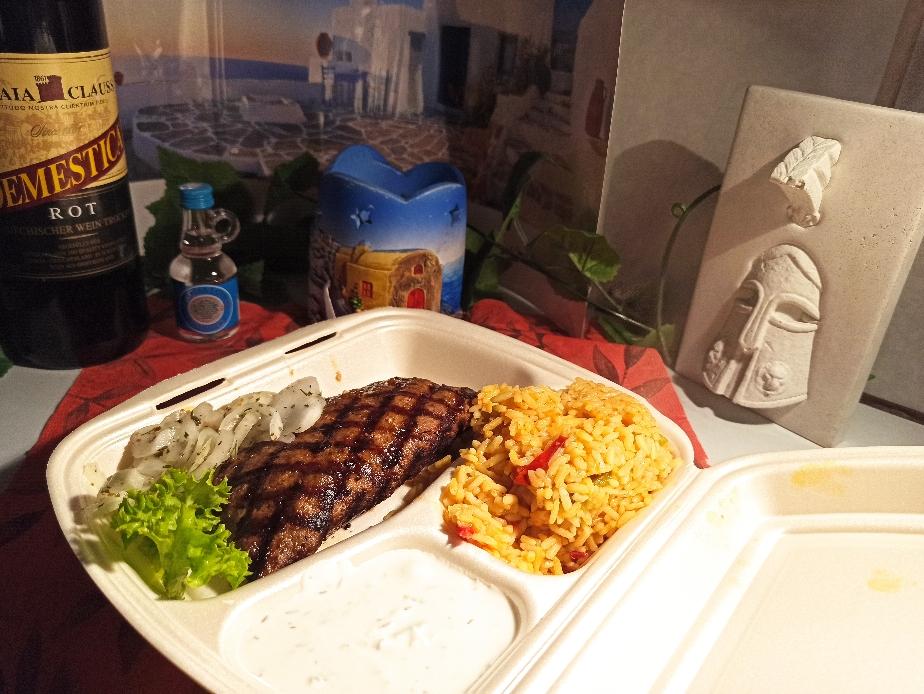 Mit griechischem Feta gefülltes Bifteki, dazu Reis, Zwiebeln und Zaziki