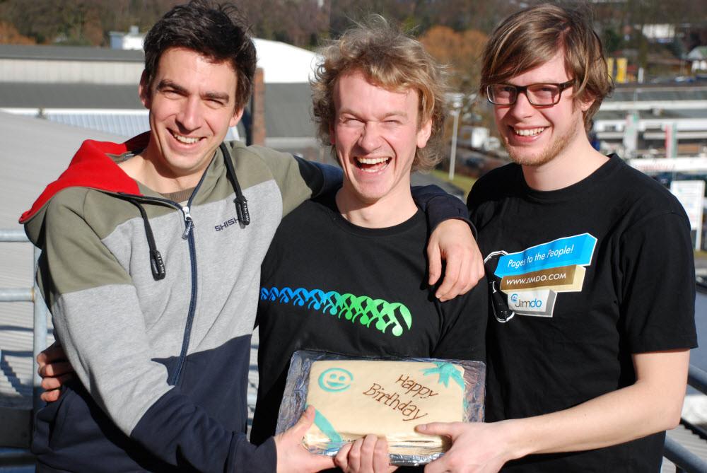 Drei stolze, gut gelaunte Gründer auf ihrer Dachterrasse