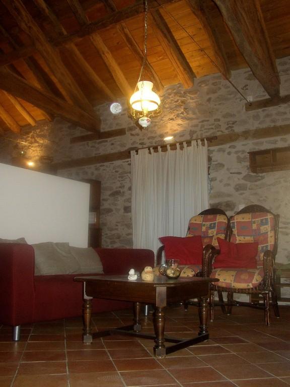 Salon avec fauteuils en rotin, canapé et poêle vitré