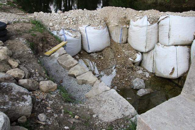 enrochement de la digue au niveau de la vanne de la rivière