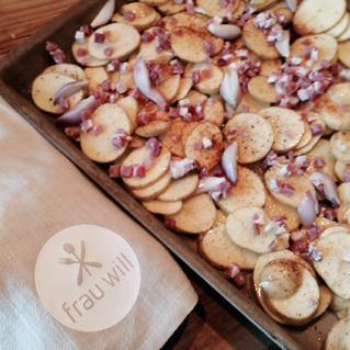Kartoffeln abtrocknen, mit Öl und Gewürzen mischen und mit den restlichen Zutaten auf dem Ofenzauberer verteilen