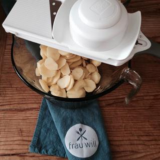 Die Kartoffeln auf Stufe 3 hobeln und in der Sahne-Milch-Gewürz-Mischung garen