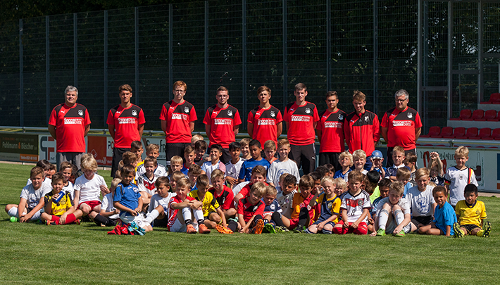 Kinder in Fußball-Kleidung sitzen auf einem Rasen. Dahinter stehen 9 Trainer des VfL Theesen.