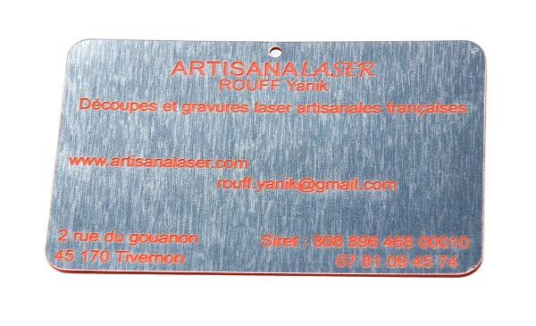 Découpe et gravure laser métal synthétique imitant l'acier brossé avec gravures en couleur rouge . Dimensions 85 mm x 55 mm .