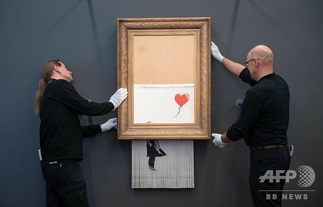 ※2:ドイツ南西部バーデンバーデンにあるフリーダー・ブルダ美術館で、細断された英国の覆面ストリートアーティスト、バンクシーの作品「愛はごみ箱の中に」を持ち上げる美術館の職員たち(2019年2月4日撮影)。