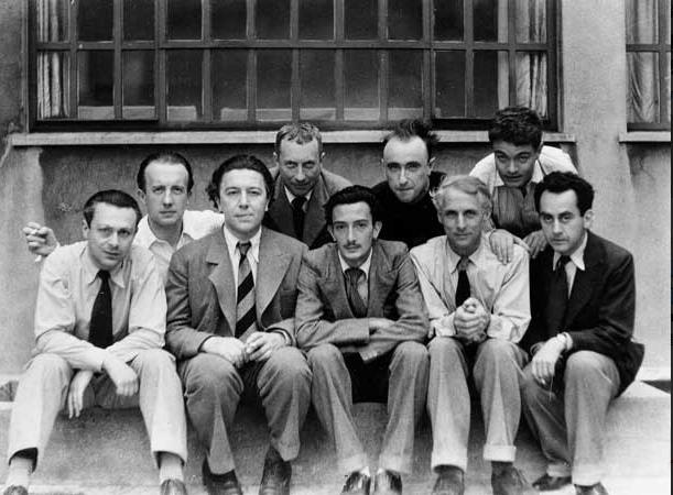 マン・レイ「シュルレアリスムのグループ」(1930年):左からトリスタン・ツァラ、ポール・エリュアール、アンドレ・ブルトン、ハンス・アルプ、サルバドール・ダリ、イヴ・タンギー、マックス・エルンスト、ルネ・クルヴェル、マン・レイ。