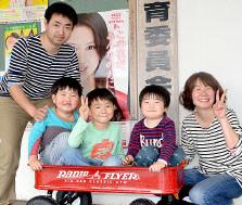 鳩間小学校へ入学する山名元太君(中央)。転入手続きのため、家族で町役場を訪れた=19日午後、町役場