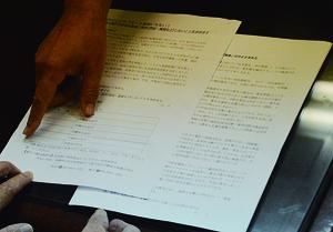 市民連絡会が署名用紙の実物(左の紙)を漢那副市長にみせた=14日、石垣市役所