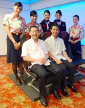 本革が採用され、高級感がアップした普通席に座る大西賢日本航空取締役会長(左)と丸川潔日本トランスオーシャン社長(6月30日)