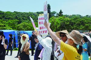沖縄全戦没者追悼式でプラカードを掲げ、安倍首相に抗議する人たち=23日午後、平和祈念公園