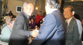 住民投票で陸自配備賛成が多数を獲得したあと、外間町長(中央)と握手する町議会の糸数議長(左)と与那国防衛協会の金城会長(右)