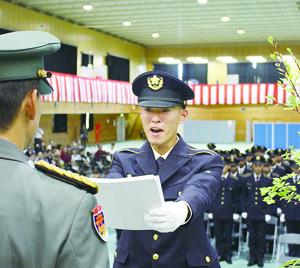 開連隊長(写真左)から修了証書を代表して授与される島袋候補生=24日、那覇駐屯地