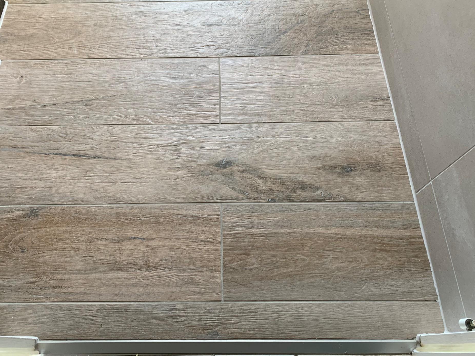 on pose le nouveau carrelage façon bois au sol et aux murs