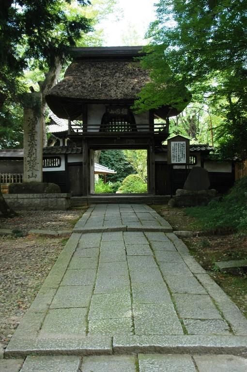御影石の参道から見た茅葺きの山門