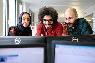 Die Amal, Hamburg!-Redakteure Nilab Langar, Omid Rezaee und Ahmad Alrifaee bei der Arbeit