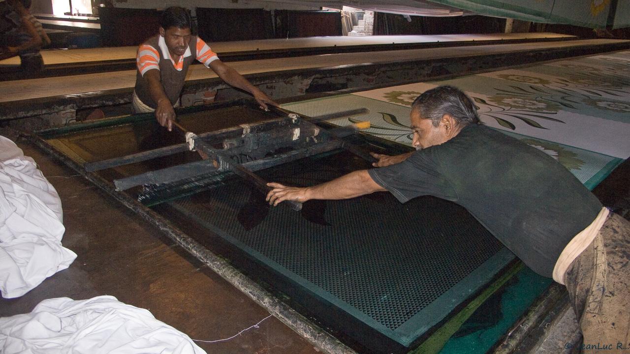 Le travail d'impression nécessite la présence de deux imprimeurs, chacun tirant à lui la raclette afin de couvrir la largeur du tissu.