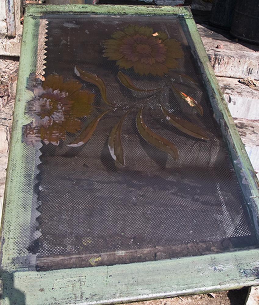 Ce cadre de sérigraphie est celui qui laisse passer la teinture verte pour l'impression du motif grillagé. Le motif floral perméable à la teinture appartient à deux autres cadres, un cadre par couleur.