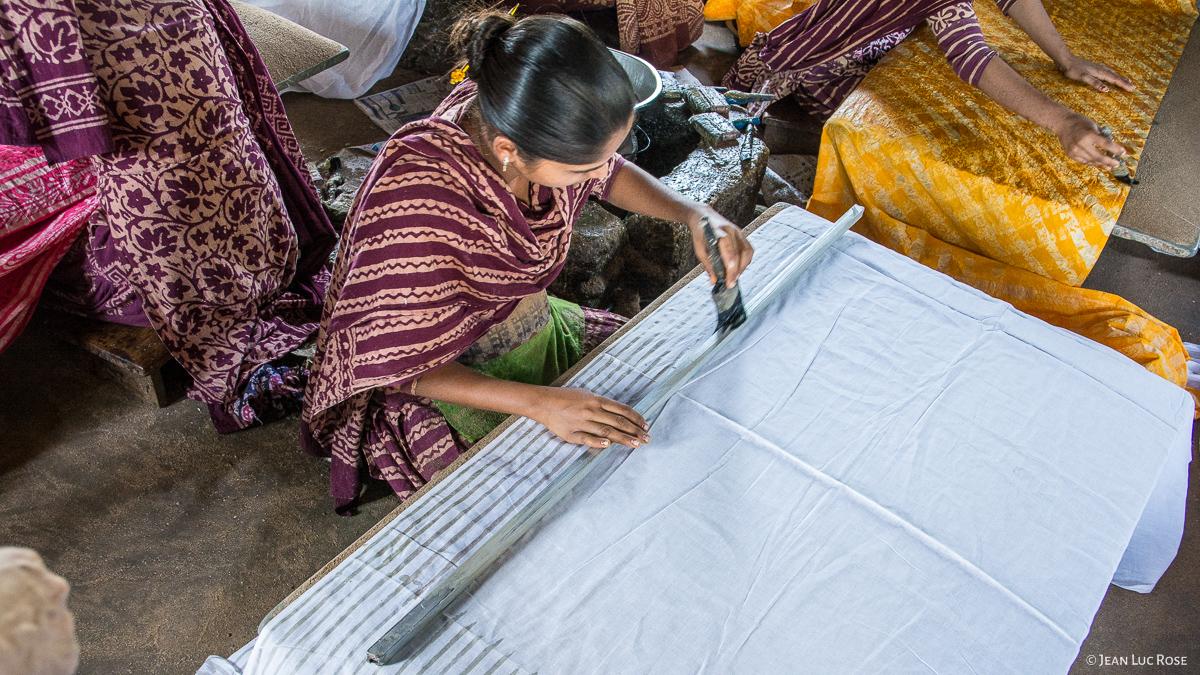 Application d'une cire chaude à l'aide d'une brosse et d'une règle pour réaliser un motif linéaire (Atelier à Bhuj / Gujarat - Inde).