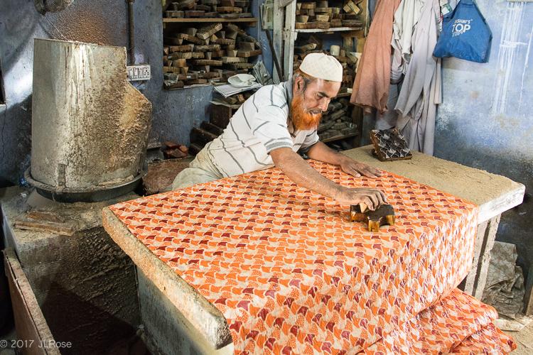 De la cire chaude est appliquée sur une partie du motif pour la préserver d'une teinture ultérieure (Bhuj / Gujarat - Inde)