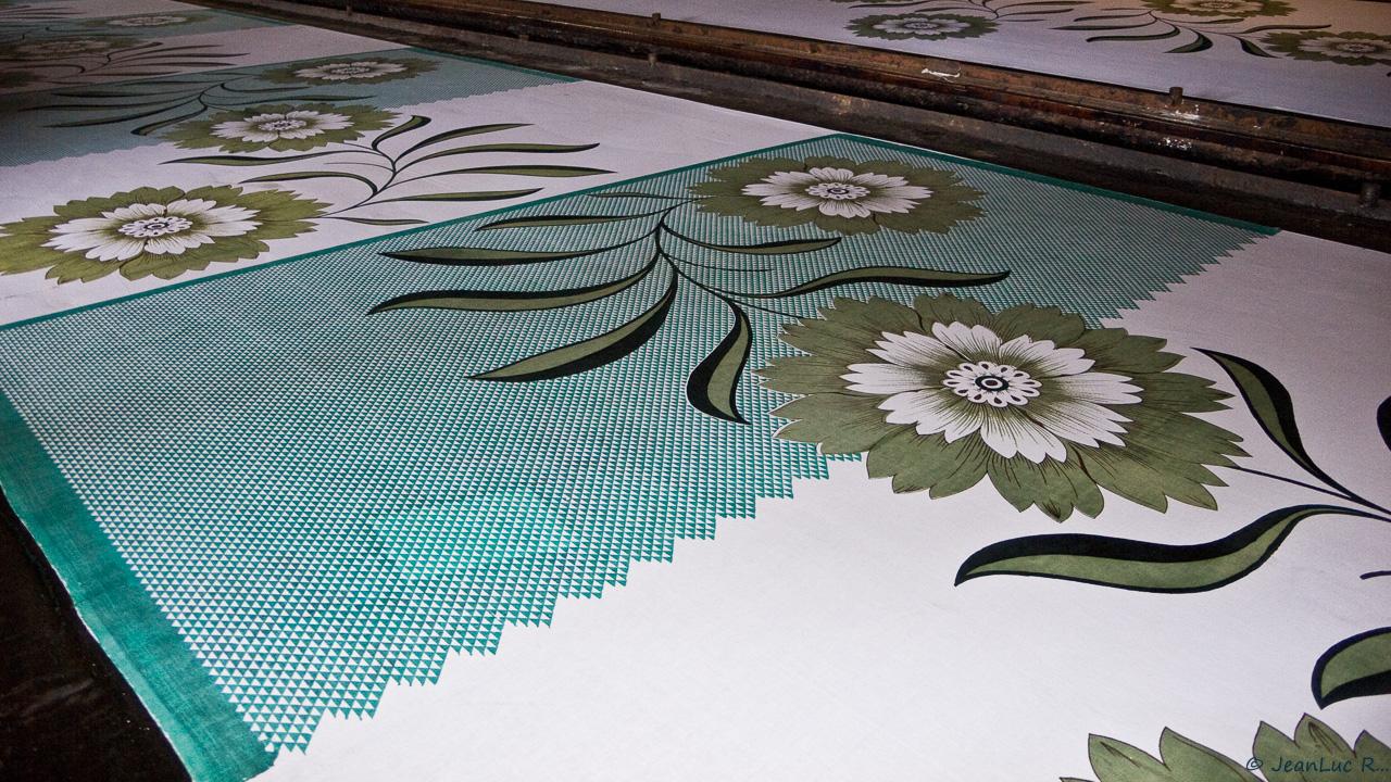 Grande fleur imprimée sur un motif grillagé vert. Le motif grillagé n'est pas encore appliqué sur toute la surface du tissu.